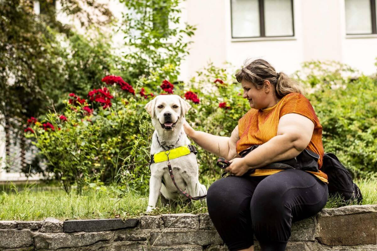 Na murku siedzi kobieta, a obok niej pies przewodnik. Kobieta głaszcze psa i się do niego uśmiecha.