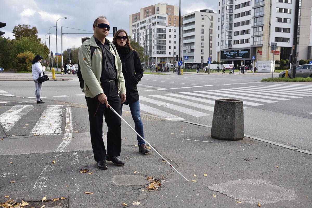 Na chodniku niewidomy mężczyzna porusza się z białą laską. Obok idzie instruktorka. W tle skrzyżowanie w mieście.
