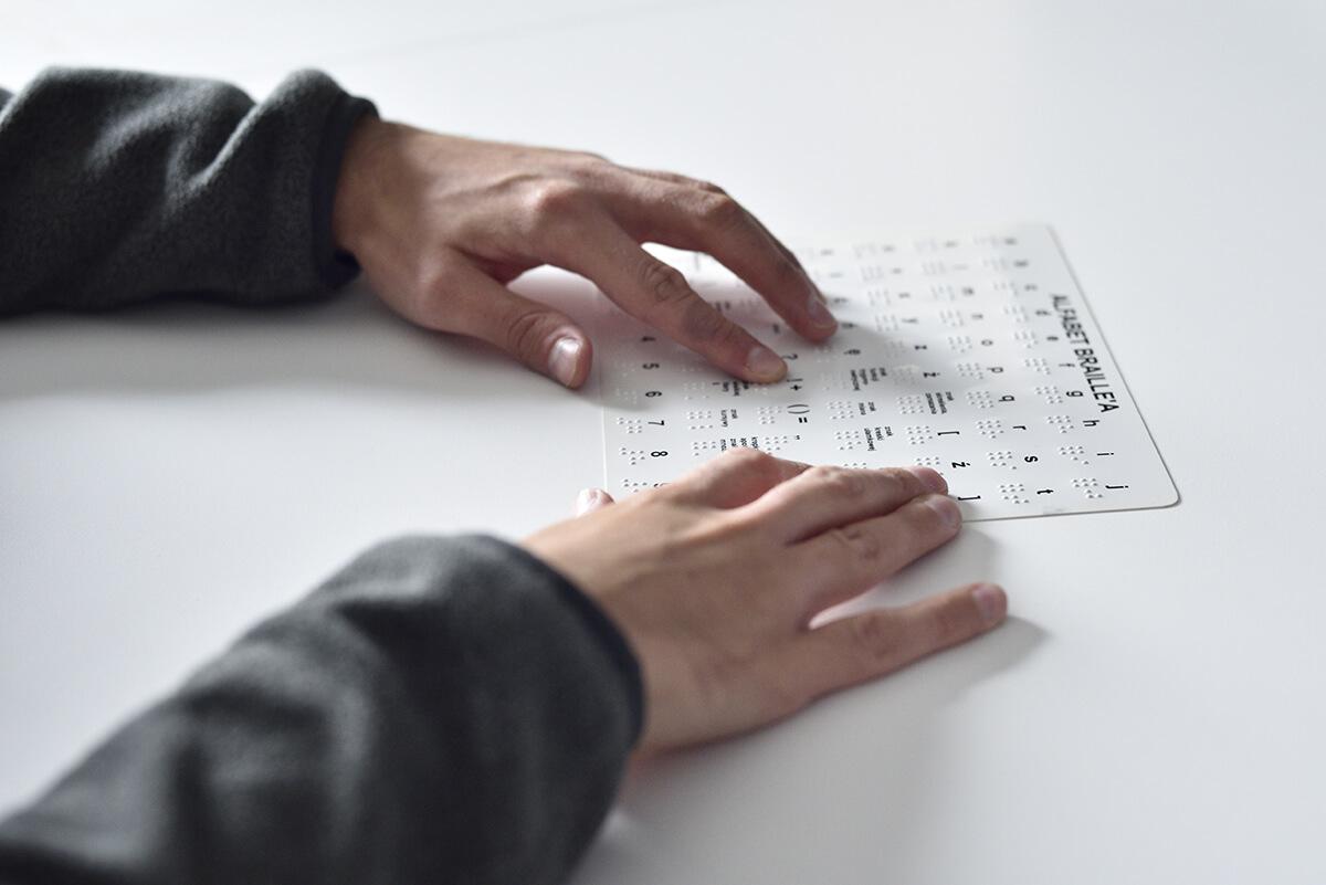 Osoba czyta alfabet Braille'a. Na zdjęciu widoczne są ręce osoby oraz tabliczka z alfabetem Braille'a.