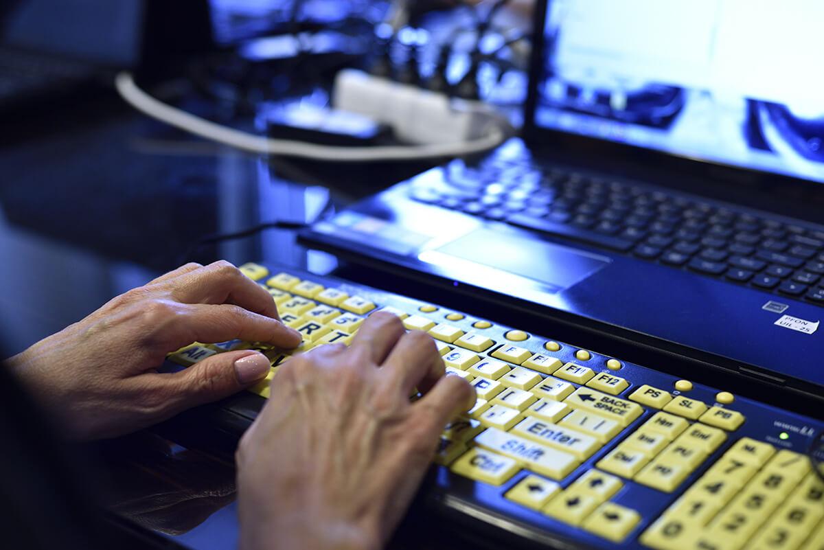 Osoba pisze na oddzielnej klawiaturze komputerowej. Na zdjęciu widoczne ręce osoby, oddzielna klawiatura i włączony laptop.