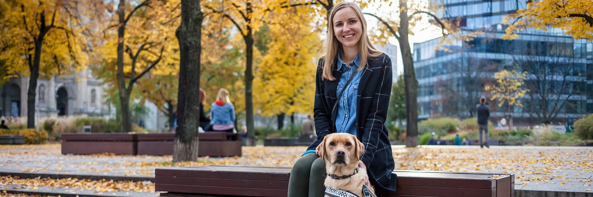 Na ławce w parku siedzi kobieta. Obok kobiety znajduje się pies przewodnik. Oboje patrzą w stronę aparatu.