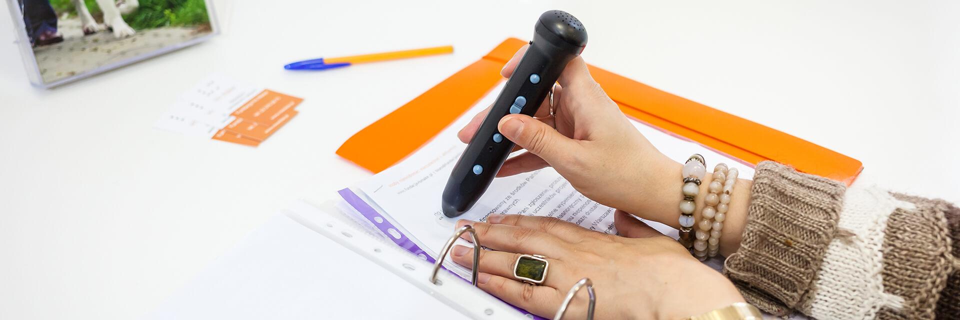 Kobieta za pomocą penfrienda odczytuje tekst na etykiecie. Etykieta przyklejona jest do koszulki, w której znajduje się dokument.