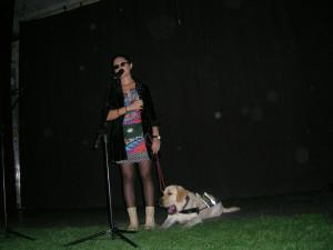 Kobieta w ciemnych okularach stoi przy mikrofonie. Obok leży pies przewodnik.