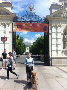 Przed bramą Uniwersytetu Warszawskiego stoi kobieta z psem przewodnikiem