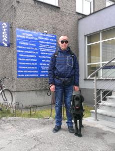 Przy schodach prowadzących do wejścia do budynku stoi mężczyzna w ciemnych okularach z psem przewodnikiem