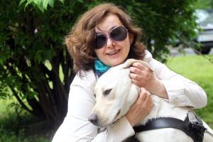 Kobieta w ciemnych okularach przytula psa przewodnika