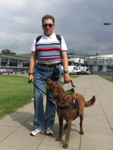Mężczyzna na chodniku z psem przewodnikiem