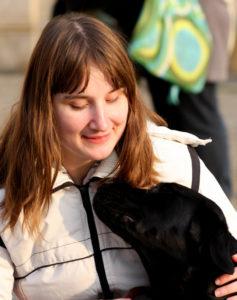 Kobieta uśmiecha się do swojego psa przewodnika. Pies patrzy na nią.