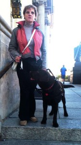 Kobieta stoi wraz z psem przewodnikiem