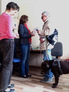 Mężczyzna w ciemnych okularach rozmawia z kobietą. Obok stoi pies przewodnik.