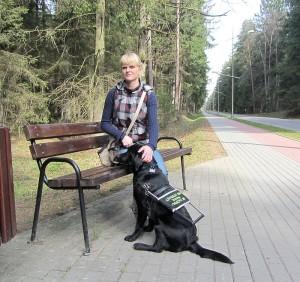 Kobieta siedzi na ławce z psem przewodnikiem