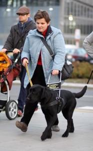 Kobieta idzie chodnikiem z psem przewodnikiem
