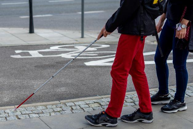 Osoba z laską wraz z instruktorem idzie wzdłuż ścieżki dla rowerzystów. Trwa kurs orientacji przestrzennej.